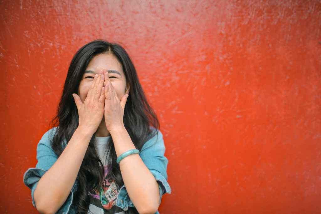 cheerful-ethnic-woman-against-vivid-red-painted-wall-3768892